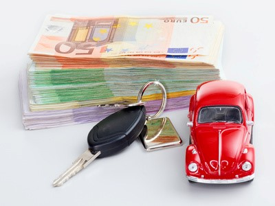 Car with car key and stacked money to show the cost increase